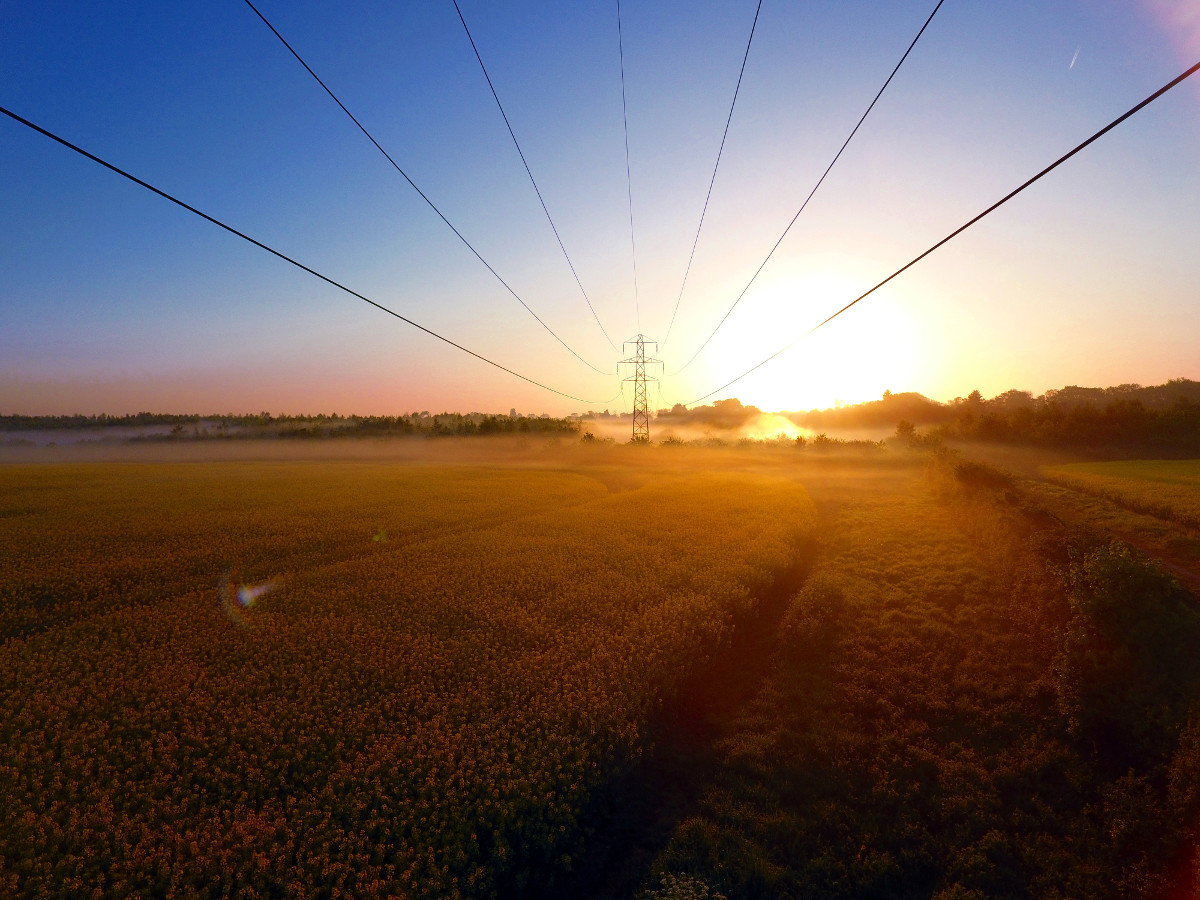 Drone photo of the sunrise taken under power lines