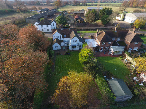 An aerial view of a house and grounds on a sunny autumn day, taken by a drone
