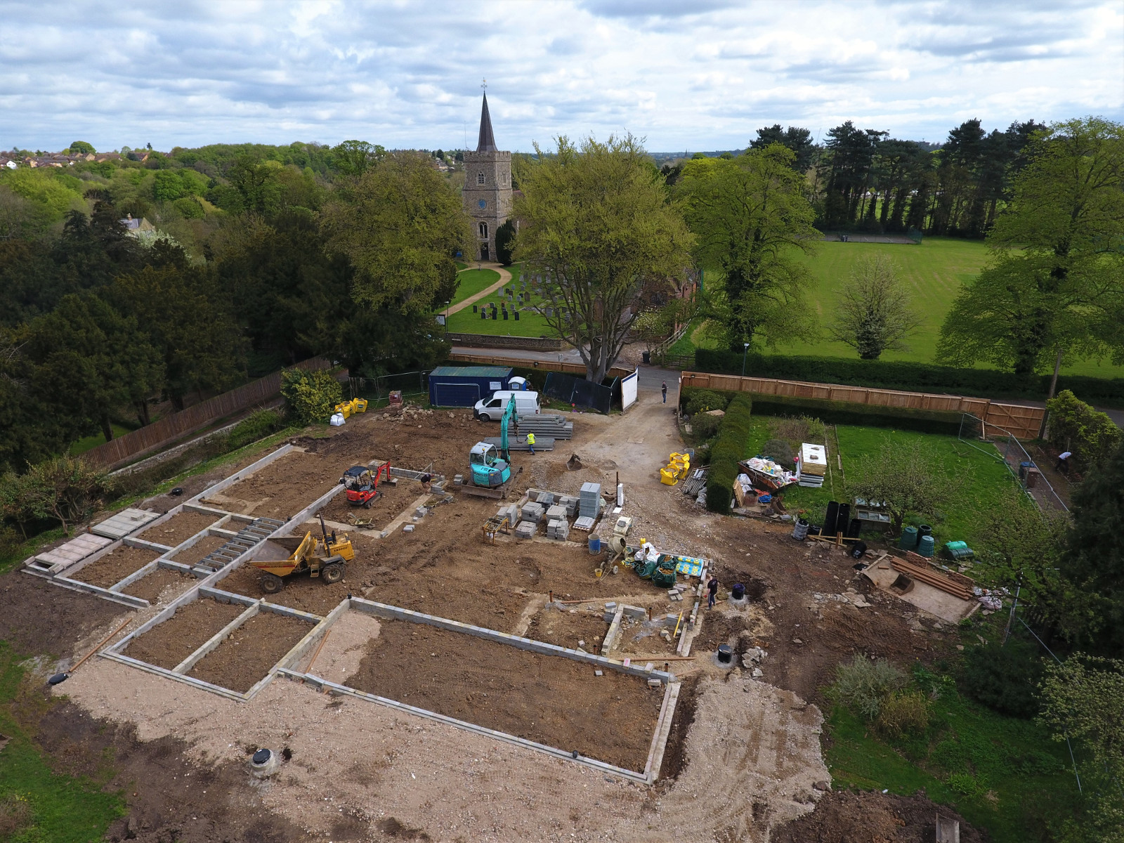 Drone photo of a building site at ground level, with a church spire between the trees in the background