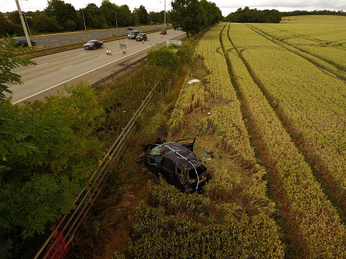 A badly damaged car lies in a field at the side of the motorway